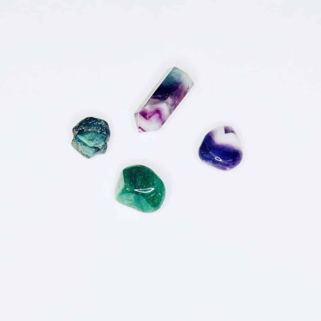 Four crystals laying on a white table - amethyst, green aventurine, fluorite, and emerald.