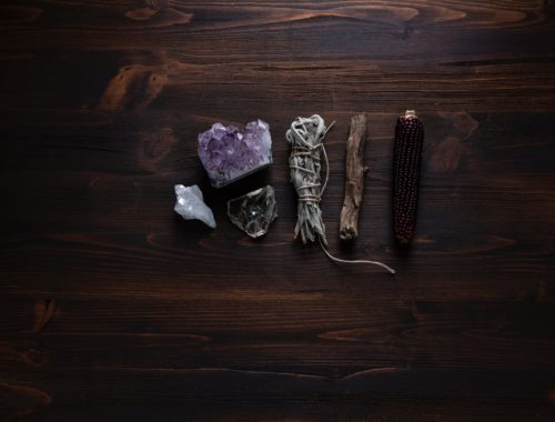 various energy clearing tools - crystals, sage, palo santo, lying on a wooden table